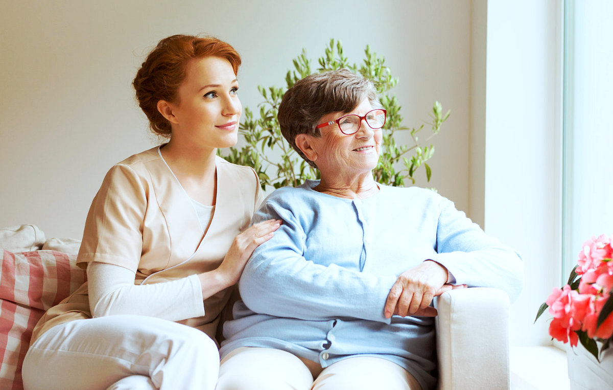 caregiver and senior woman looking outside