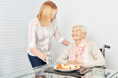 adult woman preparing meal for senior woman