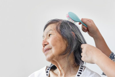 a person combing the hair of senior woman