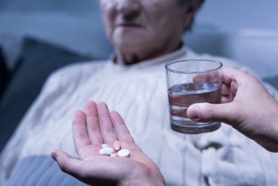 a person holding some pills and a glass of water