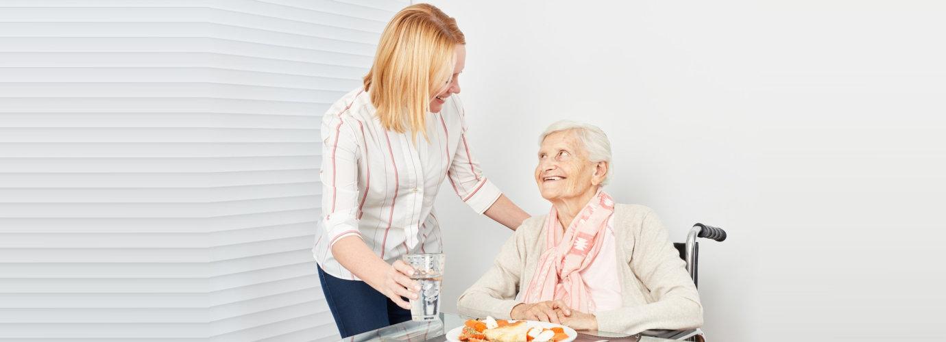 adult woman preparing meal for senior woman